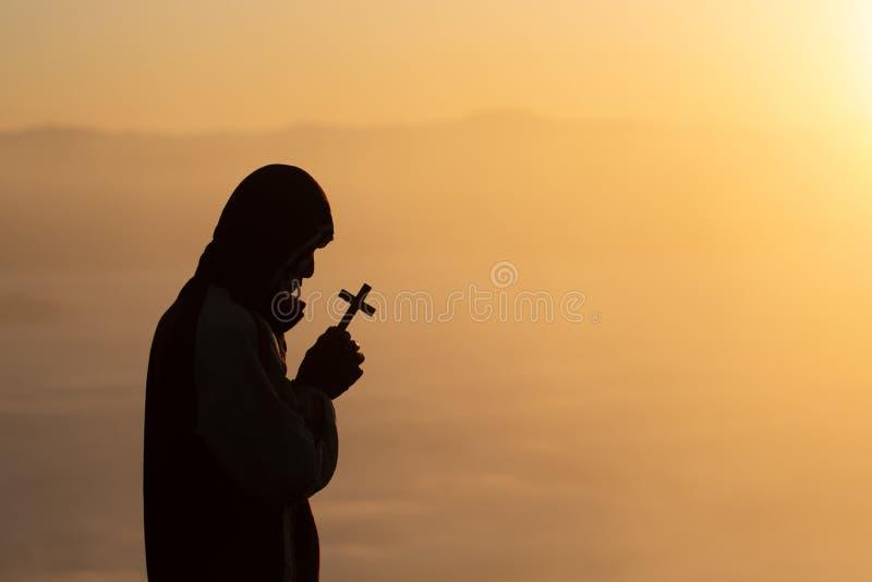 Schattenbild des christlichen jungen Mannes, der mit einem Kreuz bei Sonnenaufgang, Christian Religions-Konzepthintergrund betet lizenzfreie stockbilder