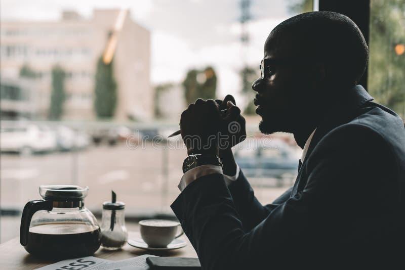 Schattenbild des durchdachten Afroamerikanergeschäftsmannes lizenzfreie stockfotografie