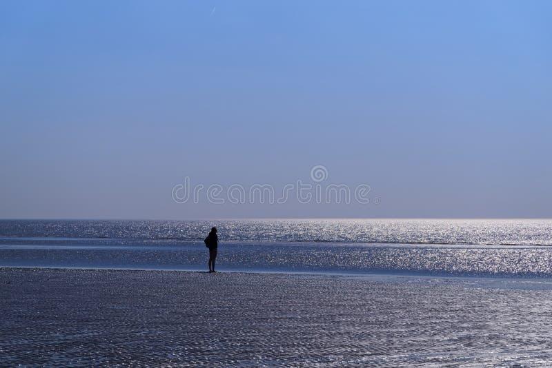 Schattenbild des einzelnen Menschen auf dem Strand, der in Richtung des Horizontes blickt stockfotos