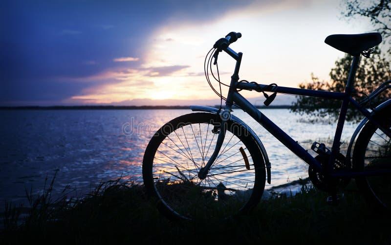 Schattenbild des Fahrrades nahe See lizenzfreie stockbilder