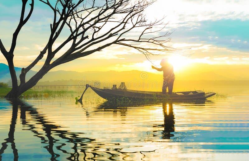 Schattenbild des Fischers, der Fischnetzstellung im Ohr des kleinen Bootes verwendet lizenzfreie stockfotografie
