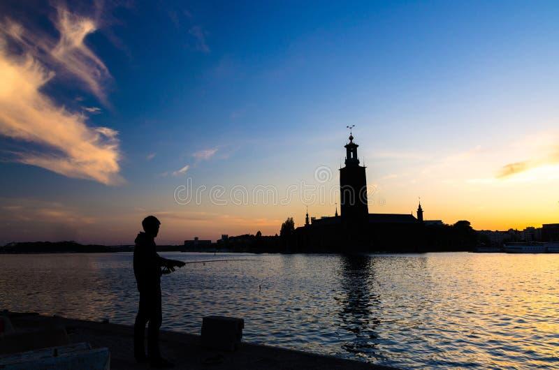 Schattenbild des Fischers mit Pfosten und StockholmRathaus, Schwede lizenzfreie stockfotografie
