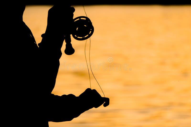 Schattenbild des Fliegenfischers bei Sonnenuntergang lizenzfreie stockfotos
