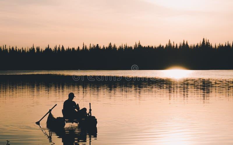 Schattenbild des Fliegenfischers bei Sonnenuntergang lizenzfreie stockfotografie