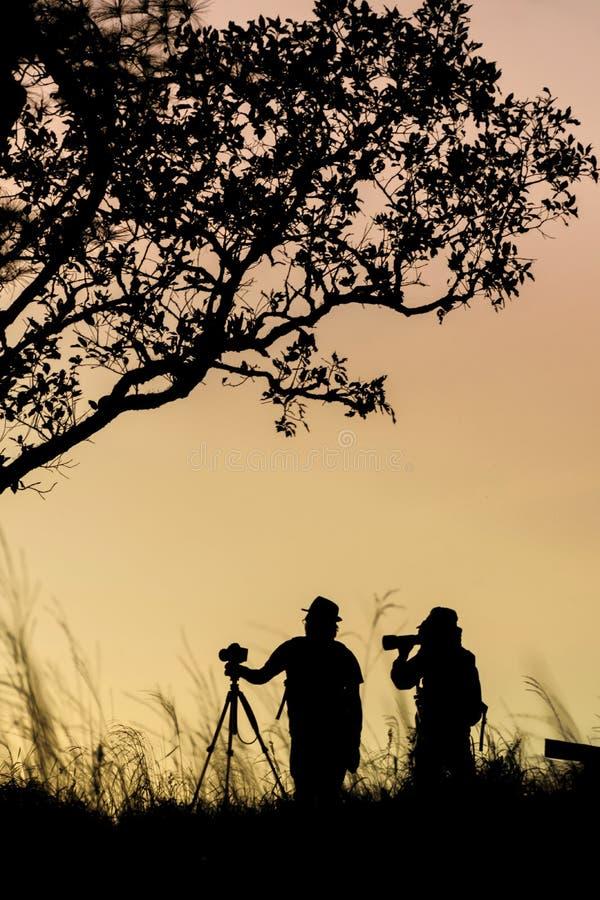 Schattenbild des Fotografen Foto der Landschaft w?hrend des Sonnenaufgangs machend stockbild
