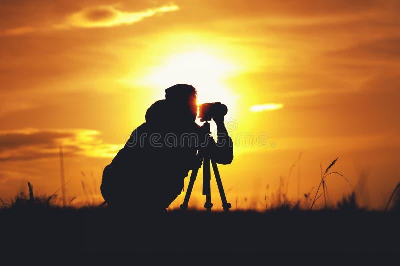 Schattenbild des Fotografen mit Kamera und Stativ stockfotografie