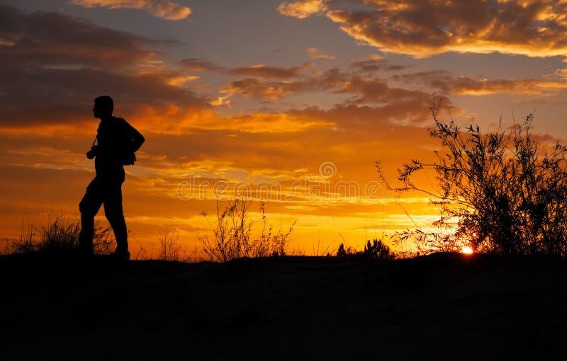 Schattenbild des Fotografen mit seiner Kamera bei Sonnenuntergang lizenzfreie stockfotografie