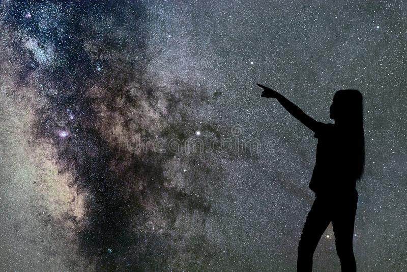 Schattenbild des Frauenstands allein in der Nachtmilchstraße und -sternen stockfoto