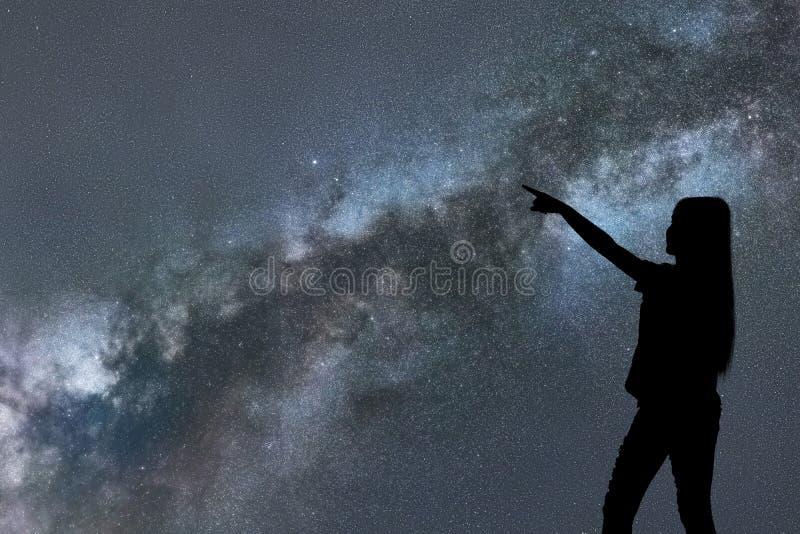 Schattenbild des Frauenstands allein in der Nachtmilchstraße und -sternen stockbilder