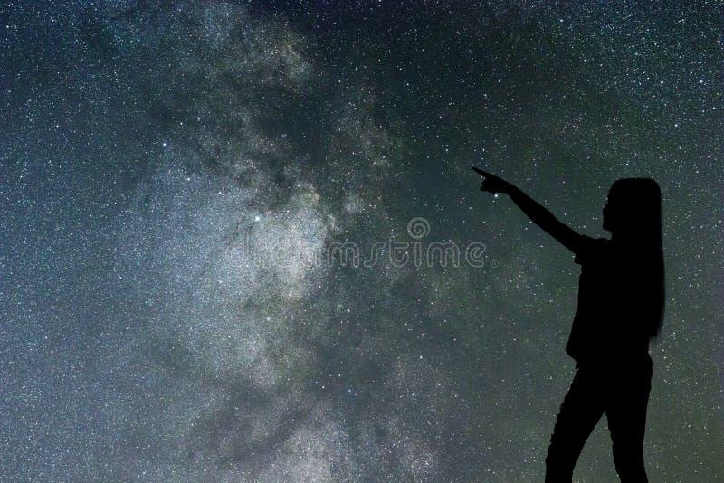 Schattenbild des Frauenstands allein in der Nachtmilchstraße und -sternen stockfotografie