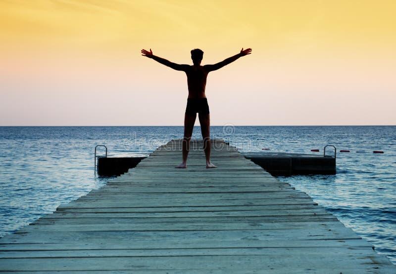 Schattenbild des freien ruhigen Mannes am Sonnenuntergang