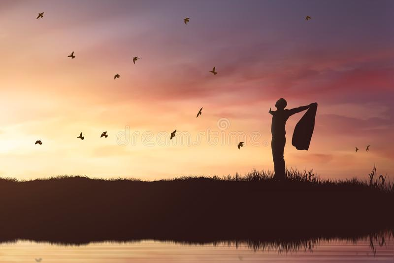 Schattenbild des Geschäftsmannes die Sonne genießend, die mit Fliegenvögeln scheint stockfoto