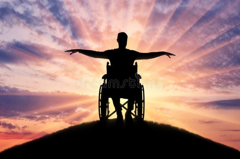 Schattenbild des glücklichen behinderten Mannes im Rollstuhl auf Hügel stockfotografie