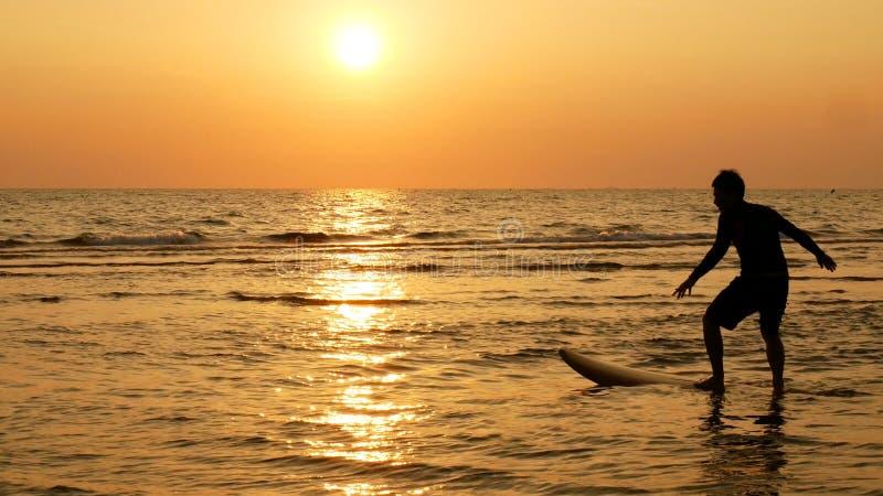 Schattenbild des glücklichen Brandungsmannes, der mit langen Brandungsbrettern bei Sonnenuntergang auf tropischem Strand surft lizenzfreie stockfotos