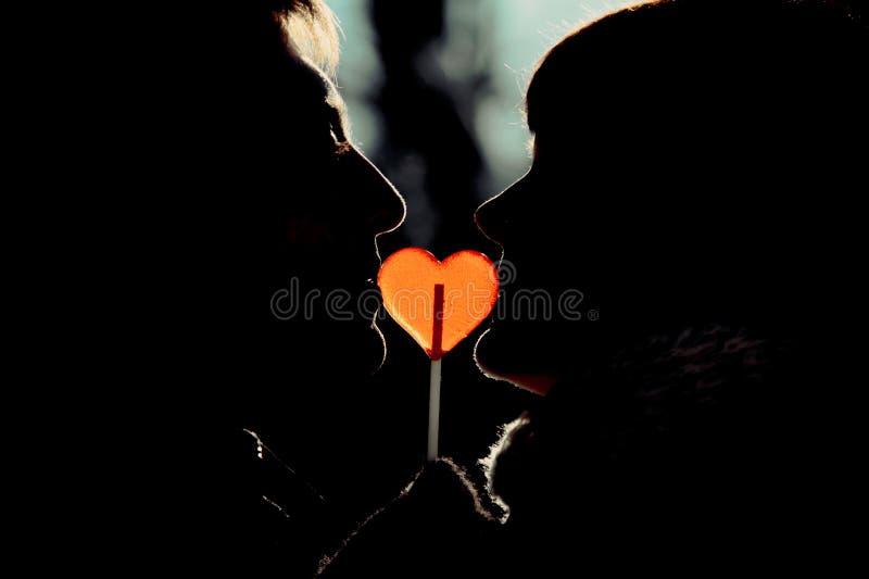 Schattenbild des glücklichen Paars im Liebeskussherz-Formlutscher stockfoto