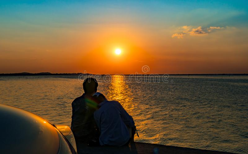 Schattenbild des Glückpaarsitzens und -entspannung auf dem Strand lizenzfreie stockbilder