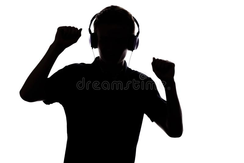 Schattenbild des Jugendlichen hörend Musik in den Kopfhörern und im danc lizenzfreie stockfotografie