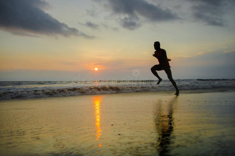 Schattenbild des jungen attraktiven Sitzes athletisch und des starken schwarzen afroen-amerikanisch am Sonnenuntergangstrandtrain lizenzfreie stockfotos