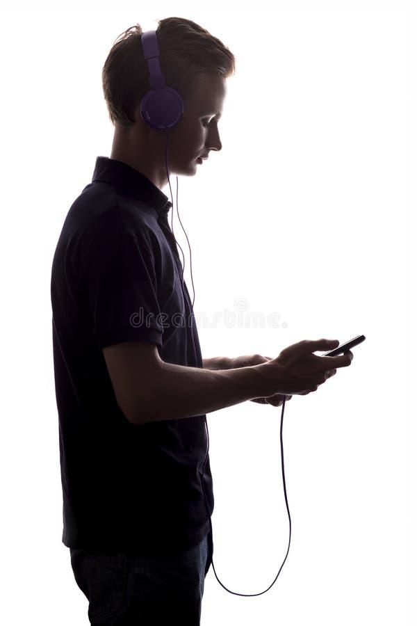 Schattenbild des Jungen in den Kopfhörern, die Titelliste von Musik auf einem Weiß leicht schlagen, lokalisierte Hintergrund lizenzfreies stockfoto