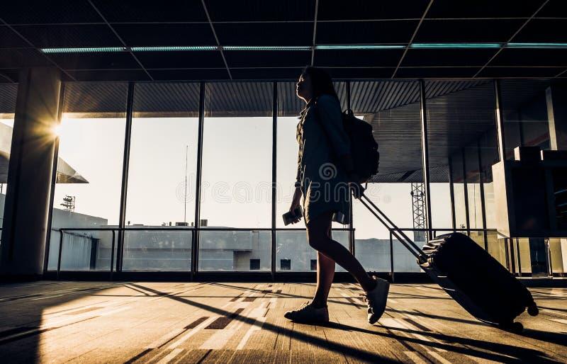 Schattenbild des jungen Mädchens gehend mit dem Gepäck, das am Flughafen geht lizenzfreies stockfoto