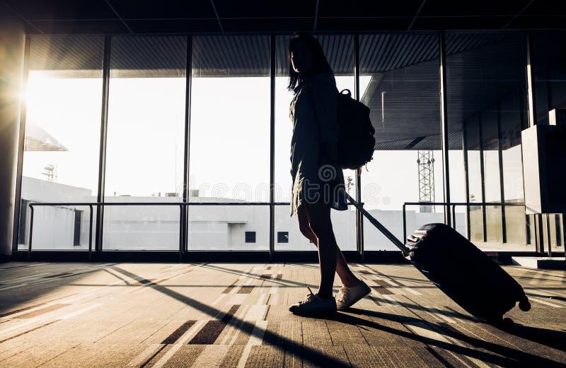 Schattenbild des jungen Mädchens gehend mit dem Gepäck, das am Flughafen geht stockbilder