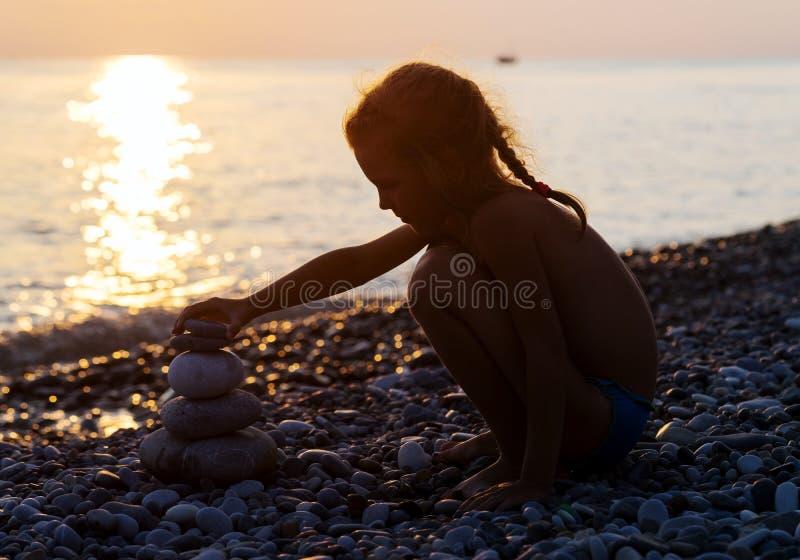 Schattenbild des jungen Mädchens setzt Pyramide von den Steinen stockfotografie
