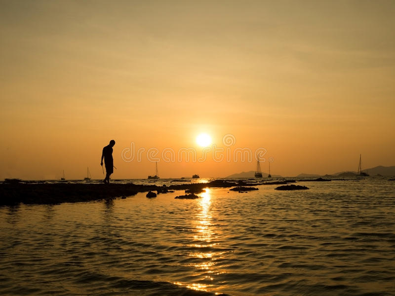 Schattenbild des jungen Mannes stehend am Seestrand mit schönem Himmelsonnenunterganghintergrund stockfotografie