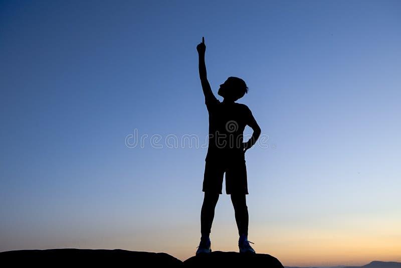 Schattenbild des Jungen zeigend auf den Himmel lizenzfreie stockfotografie