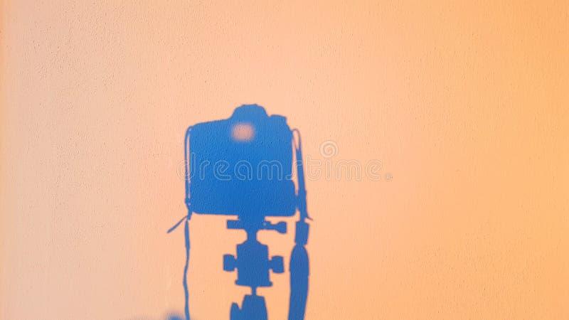 Schattenbild des Kamerareflexes auf der Wand bei Sonnenuntergang, Konzept von Technologiephotographie lizenzfreies stockfoto