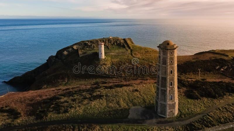 Schattenbild des kauernden Geschäftsmannes Wicklow-Kopfleuchtturm Grafschaft Wicklow irland stockfotos