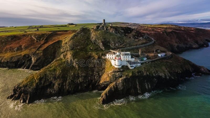Schattenbild des kauernden Geschäftsmannes Wicklow-Kopfleuchtturm Grafschaft Wicklow irland lizenzfreies stockfoto
