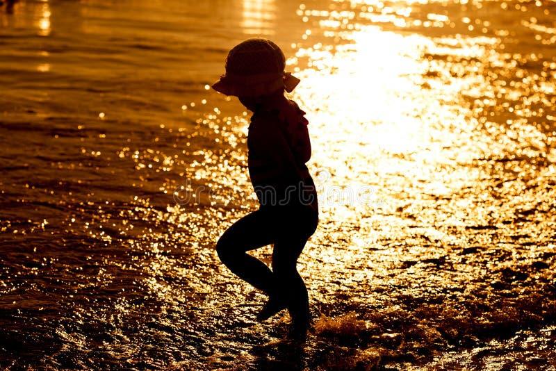 Schattenbild des kleinen Mädchens gehend am Sonnenuntergangstrand lizenzfreie stockfotografie