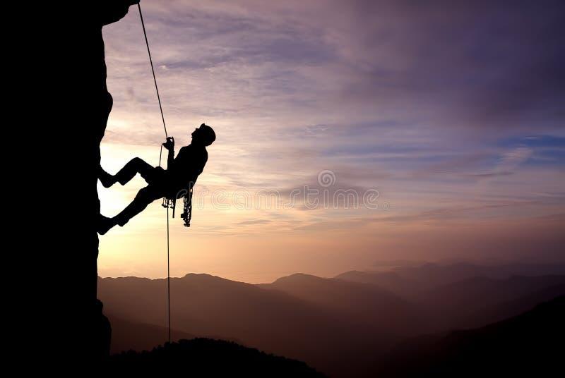 Schattenbild des Kletterers bei Sonnenuntergang stockbild