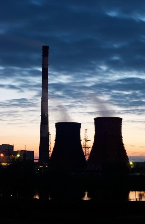 Schattenbild des Kraftwerks der Gasturbine-elektrischen Leistung gegen Sonnenunterganghimmel stockfoto