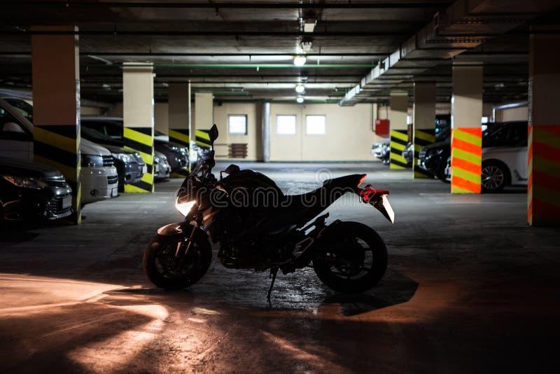Schattenbild des laufenden Maschinenmotorrades, das in der Meile Dunkelheitsuntertageparken steht Licht schaltet ein lizenzfreies stockbild
