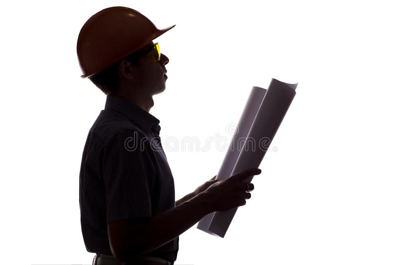 Schattenbild des männlichen Bauingenieurs mit Bauvorhaben, Mann in der Abendtoilette und Sturzhelm steuern die Arbeit über weißes lizenzfreies stockbild