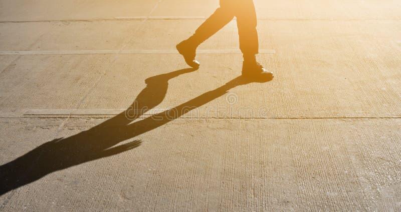 Schattenbild des Mannes gehend oder mit Schatten und Sonnenlicht tretend lizenzfreie stockfotos