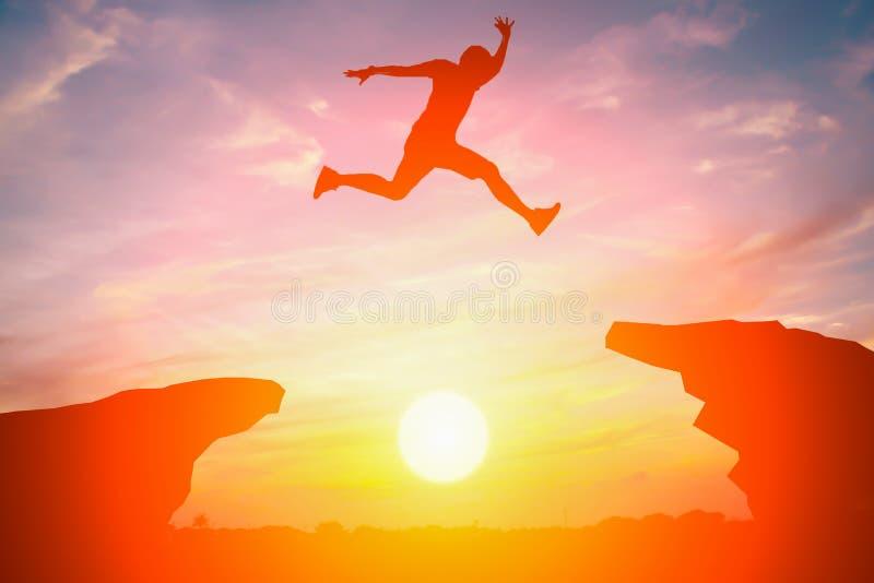 Schattenbild des Mannes springen über die Klippe stockfotografie