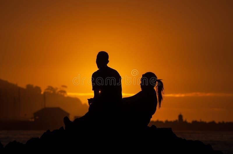 Schattenbild des Mannes und der Frauen gegen Sonnenuntergang über einem Hafen lizenzfreie stockfotos