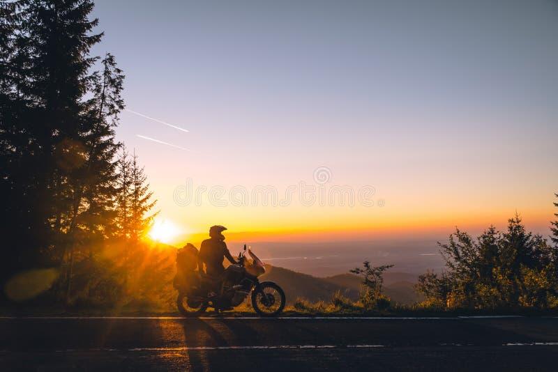 Schattenbild des Mannradfahrers und des Abenteuermotorrades auf der Straße mit Sonnenunterganglichthintergrund Spitze von Bergen, stockfotos