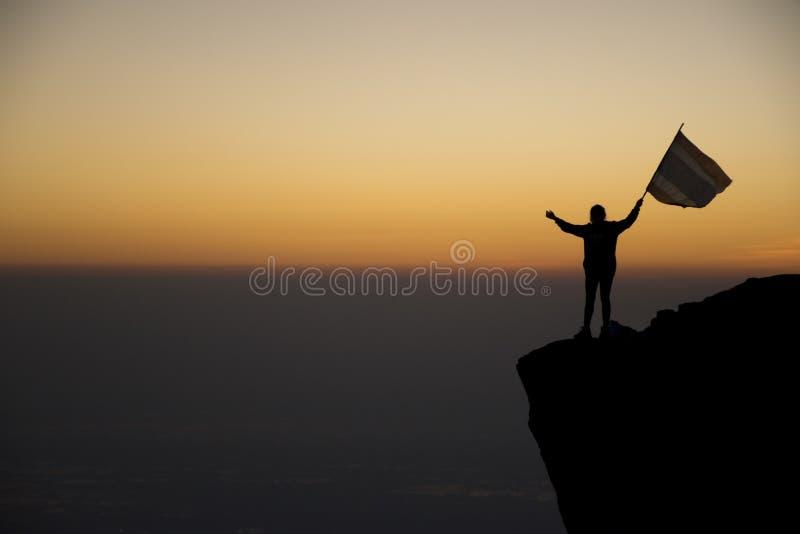 Schattenbild des Menschen und der Flagge auf dem Hügelhintergrund wenn Sonnenaufgang stockbild