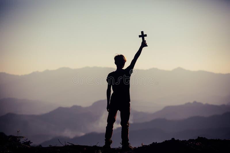 Schattenbild des menschlichen Handholdingkreuzes, der Hintergrund ist- der Sonnenaufgang , Konzept f?r Christen, stockbilder