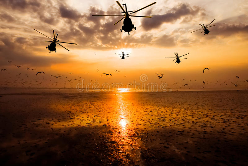 Schattenbild des Militärhubschraubers, der in Himmel bei Sonnenuntergang sich bewegt lizenzfreies stockfoto