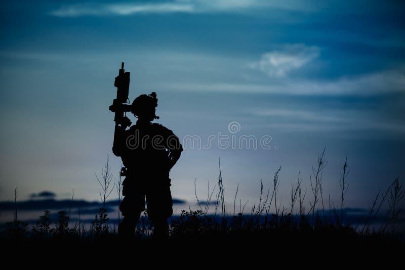 Schattenbild des Militärsoldaten oder des Offiziers mit Waffen nachts stock abbildung