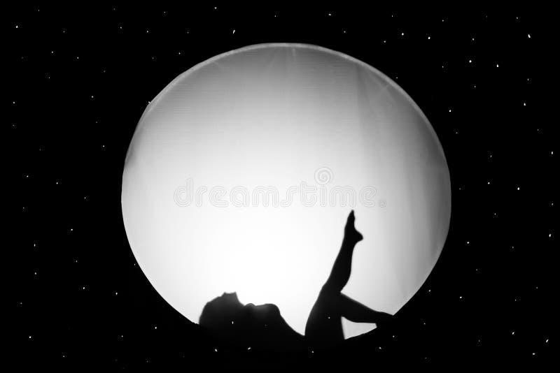 Schattenbild des nackten Mädchens, gegen einen weißen Hintergrund in Form eines Kreises im schwarzen Raum stockfotografie