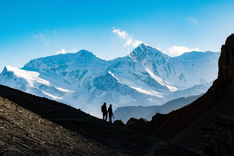 Schattenbild des Paarhändchenhaltens gegen Annapurna-schneebedeckte Berge, Himalaja stockfotografie
