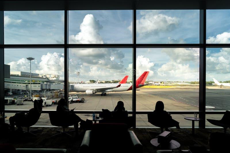 Schattenbild des Passagierwartefluges für Reise im Aufenthaltsraum an a lizenzfreie stockfotografie