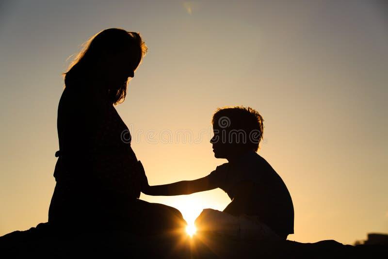 Schattenbild des rührenden schwangeren Mutterbauches des kleinen Jungen lizenzfreie stockfotos