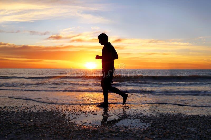 Schattenbild des ruhigen Mannes allein laufend auf Strand bei Sonnenuntergang lizenzfreies stockfoto
