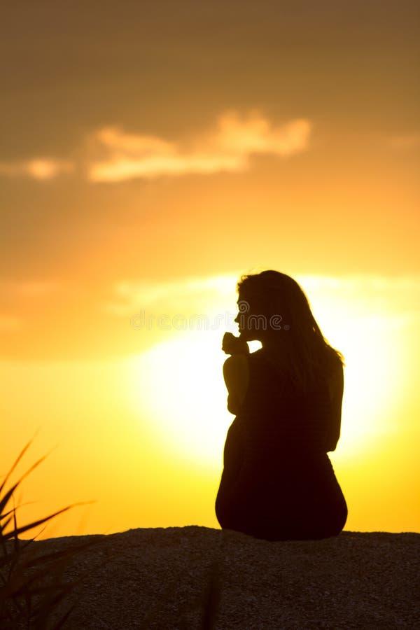 Schattenbild des schönen durchdachten Mädchens, das auf dem Sand sitzt und den Sonnenuntergang, die Zahl der jungen Frau auf dem  stockfotografie